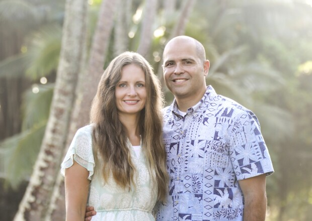 Monica and John Kauwe stand together smiling in an aloha shirt and dress with palm trees in the background.