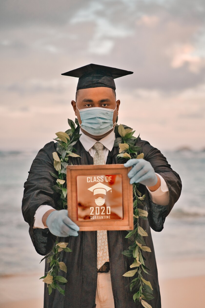 "Justin holding a brown sign saying ""Class of 2020 quarantine,"" wearing wearing blue gloves and a mask and a graduation cap and gown with the beach in the background."