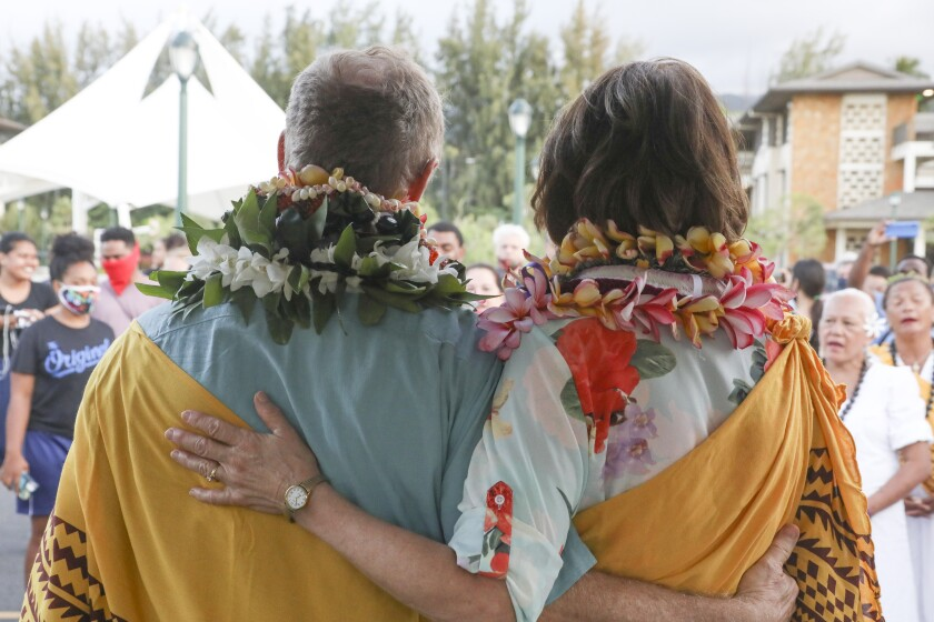 John and Susan Tanner stand with arms around each other with leis and a traditional Hawaiian yellow wrap.
