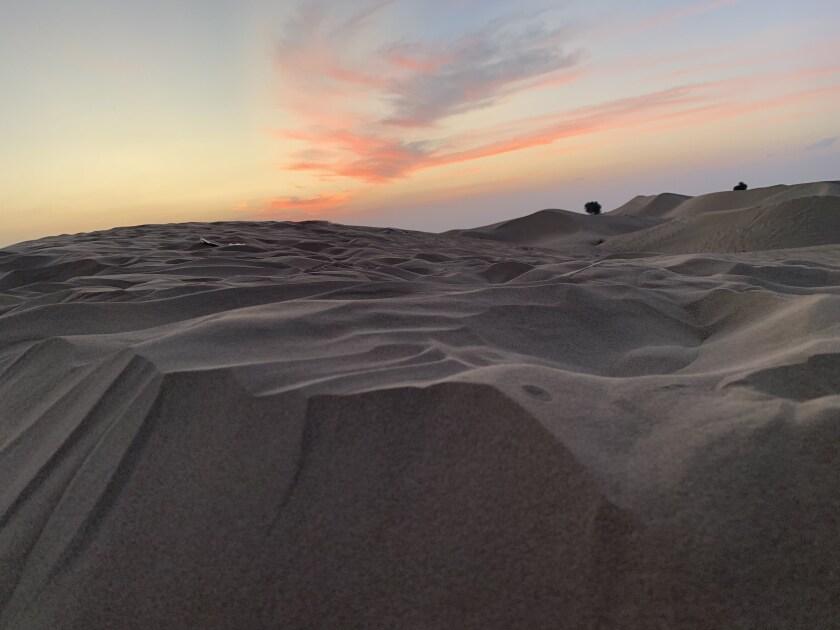 A sunset descends upon the desert in Dubai.