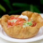 This is a photo of a taco salad. The tortilla had been fried to form a shell, shaped like a turtle's. Inside is meat, tomatoes, lettuce, and sour cream.