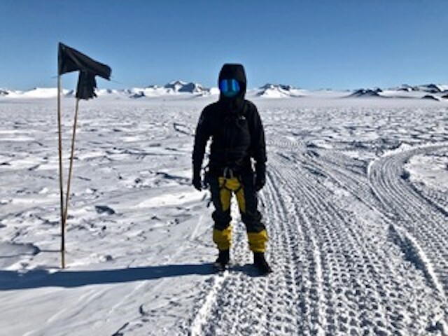 Spencer Ingley stands on ice and snow in Antarctica.