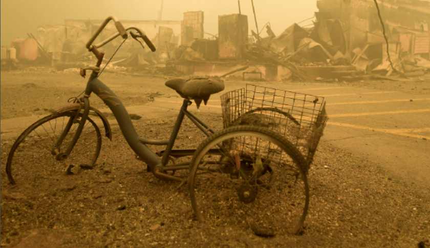 Photo of a burned down town and bike all in brown smoke haze.