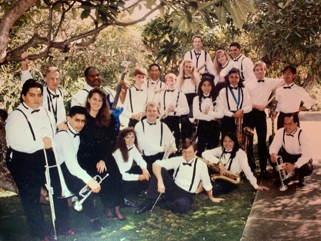 photo of Eddie Maiava in the BYUH jazz band with all the students standing under a tree wearing white button-up shirts, black bowties, black suspenders and black suit pants holding instruments.