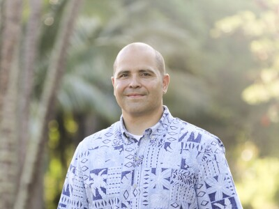 John Kauwe standing in a blue and white aloha shirt smiling with greenery in the background.