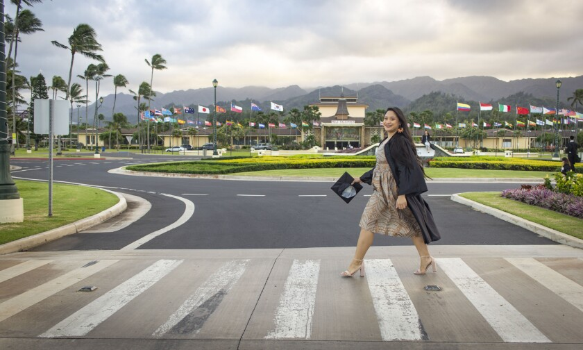 Hernaez walks across a walkway with green-fielded-roundabout and flag circle in the front of the BYUH campus, wearing a black graduation gown and holding a cap in heels and a tan and gold Polynesian designed dress.