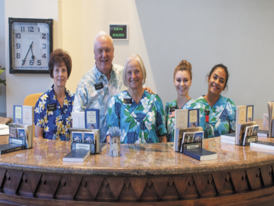 Elder and Sister Allen stand with various missionaries at the front desk of the Laie Visitors' Center