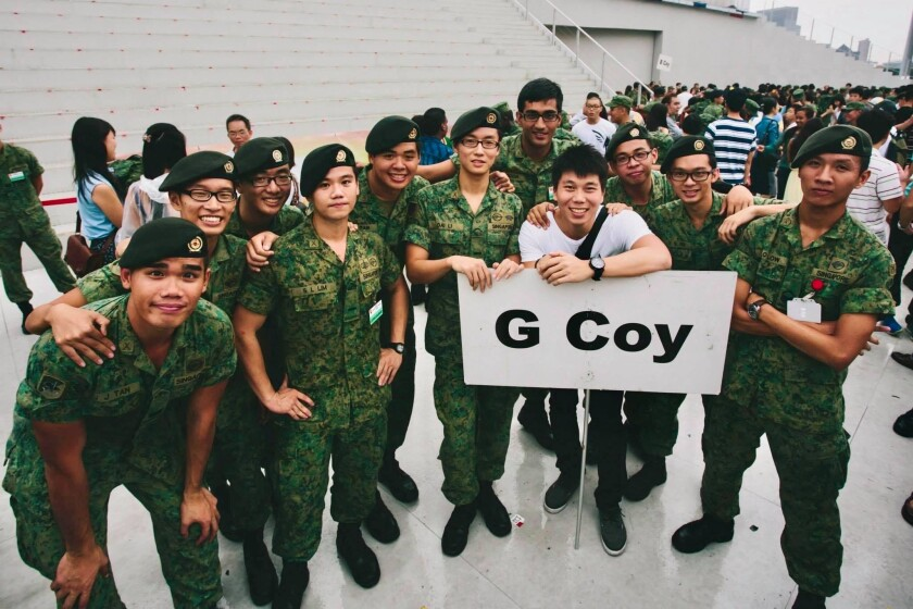 """Tan stands in military uniform with a group of other men in military uniforms with a sign saying """"G Coy."""""""