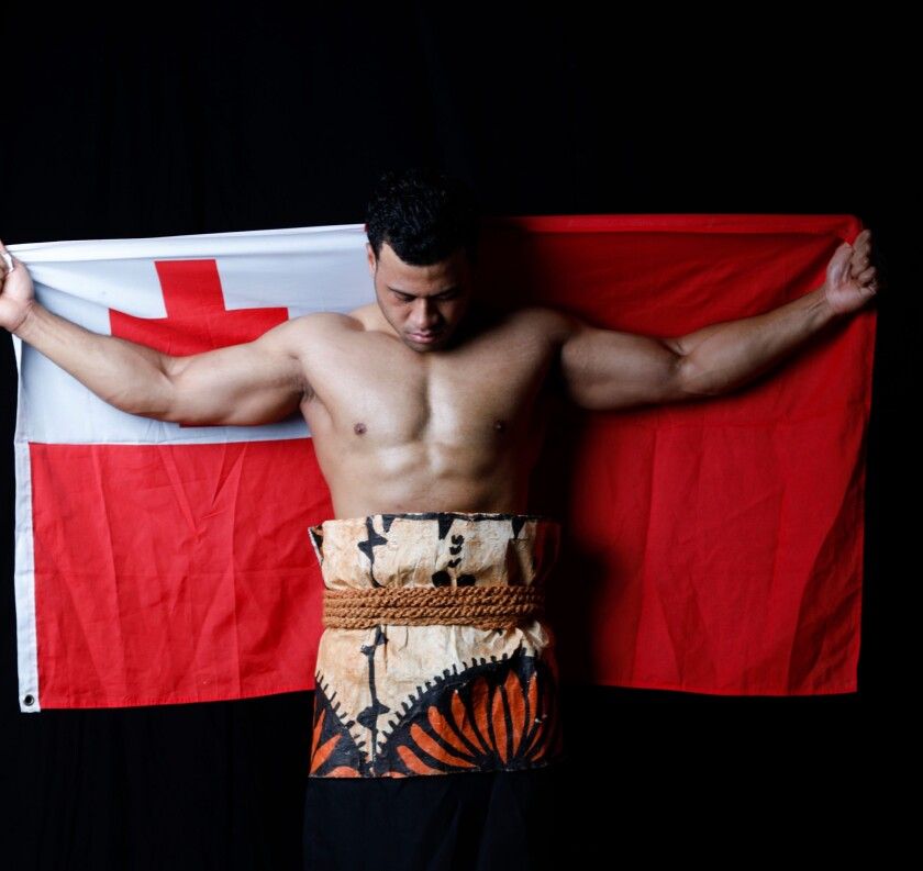 Holmes Finau holds his country's flag while dressed in traditional clothes.