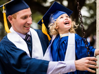 A student in graduation robes with his daughter