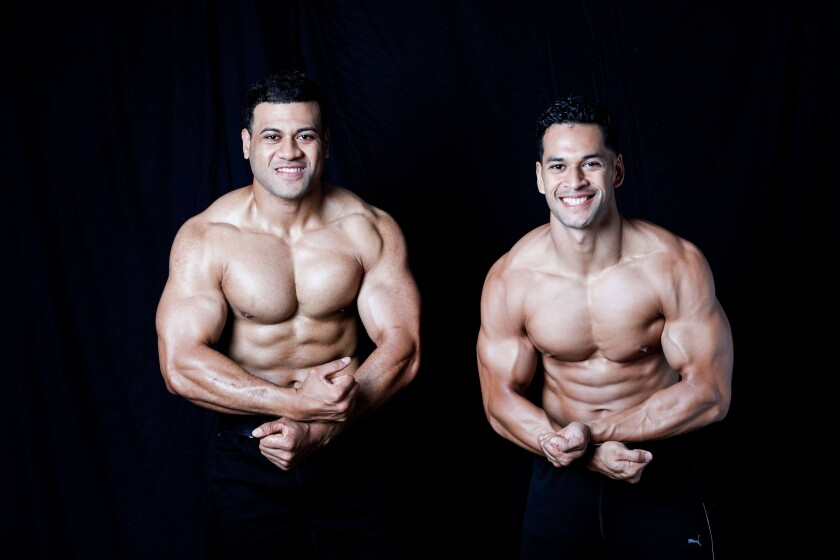 Holmes Finau and Ammon Autele flex their muscles while being shirtless.