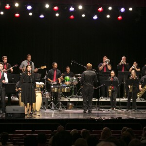 Three singers and a Latin band with trumpets, saxophones, percussion, electric guitar, and bass.