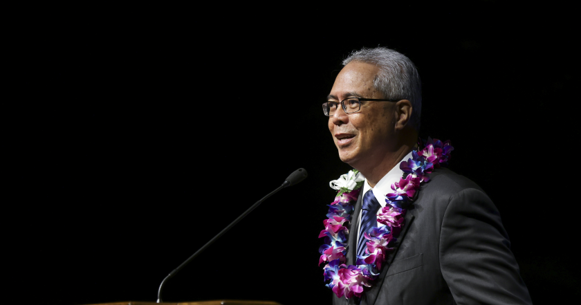 Mullaney speaking at the microphoen wearing a black suit with a blue striped tie with a purple flower lei around his neck and blackness behind him.