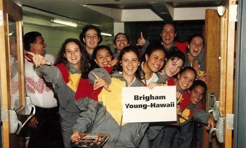 """Onze meninas em jaquetas cinza, amarelo e vermelho segurando uma placa que dizia: """"Brigham Young-Hawaii"""" e um homem segurando a porta aberta à esquerda."""