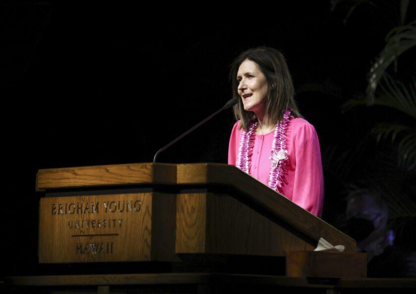 Sister Craig at the podium at BYU–Hawaii wearing a pink dress and purple lei.