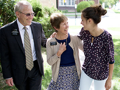 A senior missionary couple visits with a young woman.