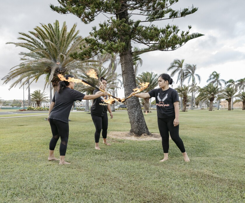 Jeralee, Ava and Chandae, all wearing the black fireknife T-shirt and black leggings, hold their lit fireknifes together while they are standing in a circle on the grass at BYUH campus.