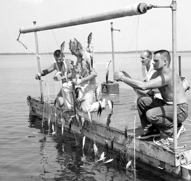 men working at fish on a net BW.jpg