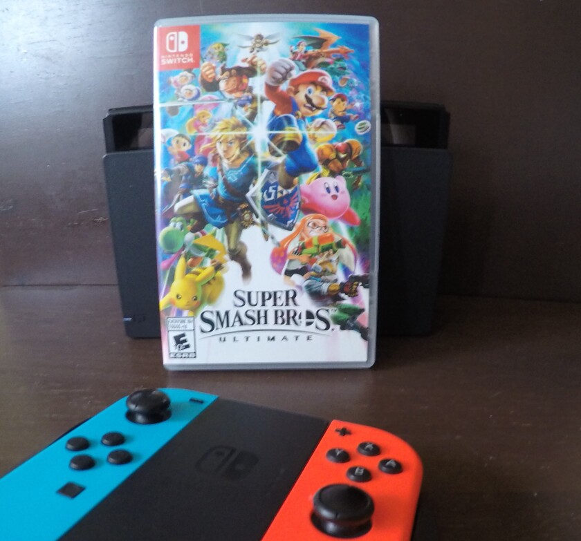 "A Nintendo Switch console, controller and ""Super Smash Bros. Ultimate"" Switch game."