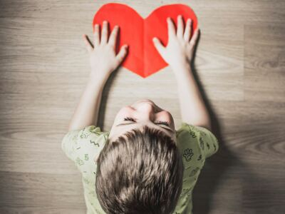 Image of a young boy laughing and holding a red paper heart