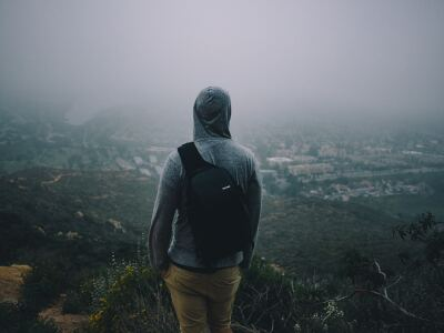 A back view of a man with a backpack looking from the top of a mountain over a city.