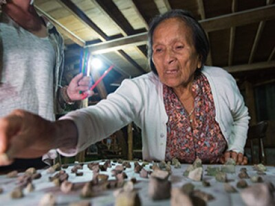 Quichua woman placing stones on a table