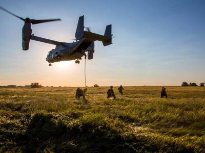 Special Operations forces train in a field with a helicopter overhead.