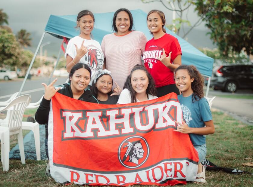 Seven girls with a Kahuku Red Raiders flag on Kulanui Street.