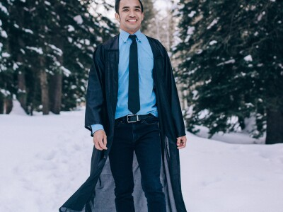 Cabral, dressed in a graduation gown, stands in front of a snow-covered tree and landscape behind him.