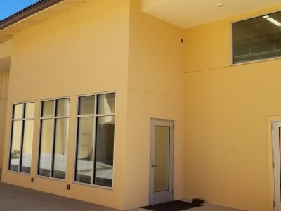 The front view of the Fitness Studio has three big windows and two glass doors. The doors look closer to the right-hand side of the photo. The outside design of Fitness Studio is complete.