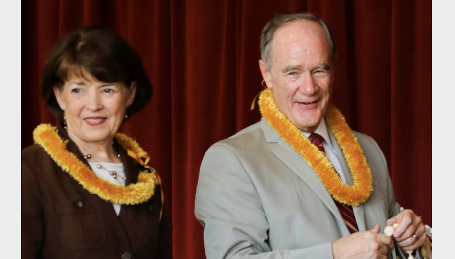 President and Sister Tanner, adorned with leis, hand out leis during the parents' reception