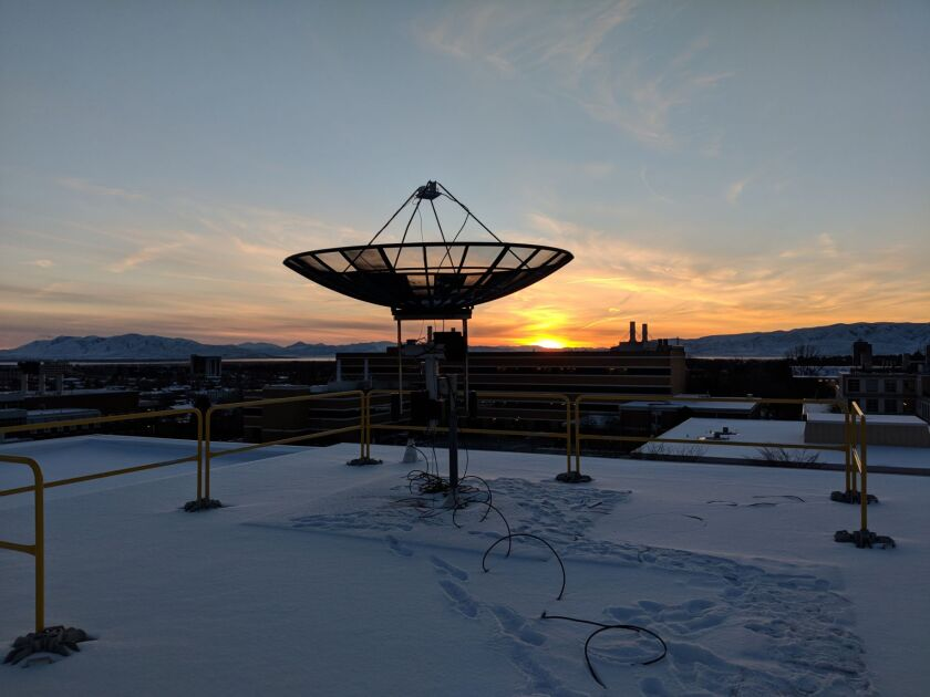 An image of a satellite on a roof with the sun setting in the background