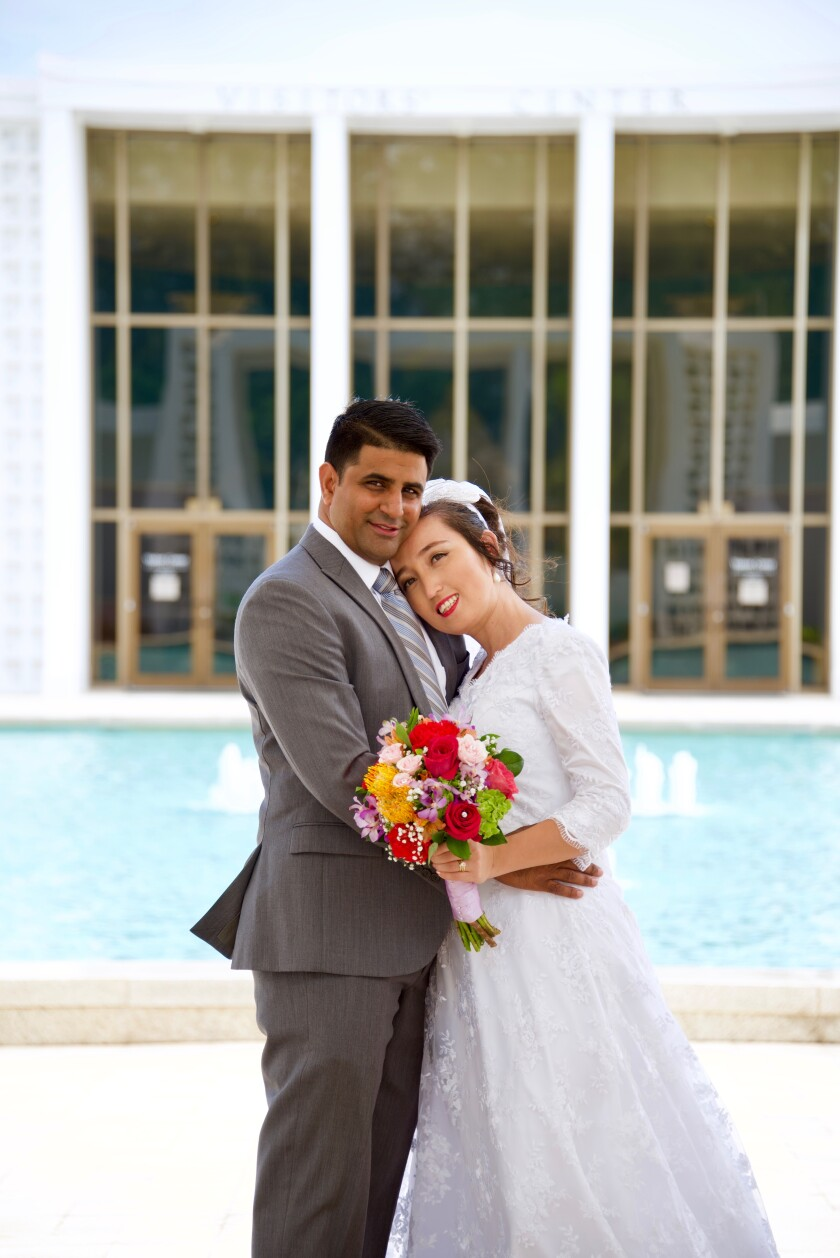 The Kumars stand newly married in a white wedding dress and suit holding a colorful flower bouquet in front of the Laie Hawaii Temple's visitor center and fountain.