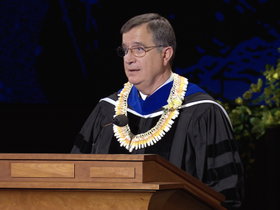 Brother Pace wearing academic robes and a lei speaking at a podium