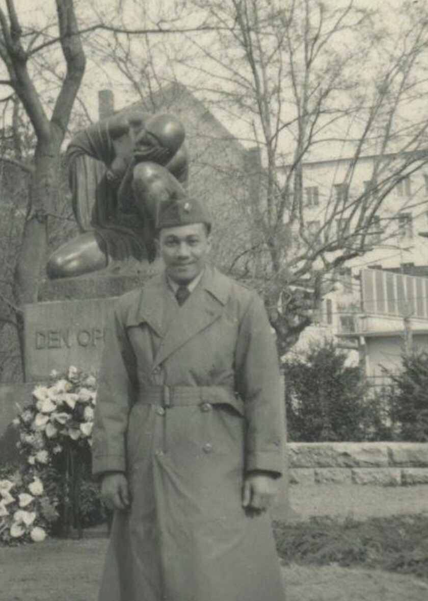 Toelupe stands in a black and white photo wearing a coat and military hat with bushes and statue behind him.