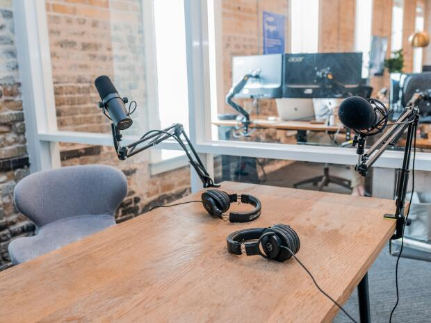 An empty podcast studio with microphones and headsets on a table.