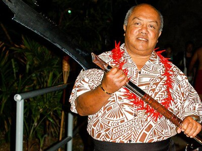 Pulefano Galea'i dressed in a Hawaiian shirt and red lei holds a Samoan fire knife next to a trophy