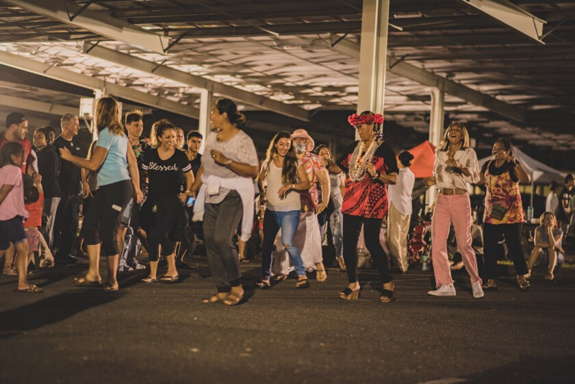 A large group of Laie community members of all ages in the BYUH admin parking lot dancing to the music with smiles on their faces.