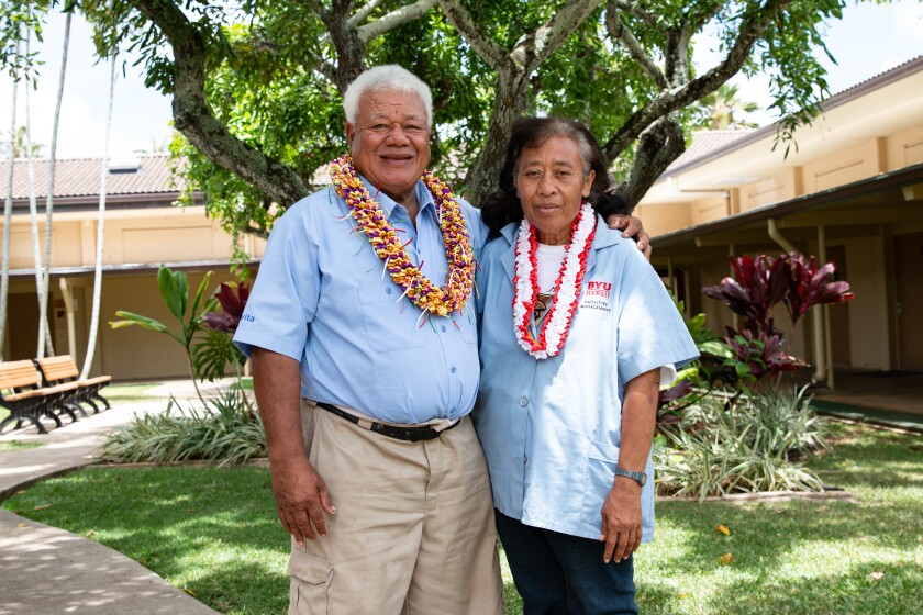 Tevita and Mele Lavulavu smiling wearing light blue button-up shirts wearing colorful leis with green and greenery behind them.