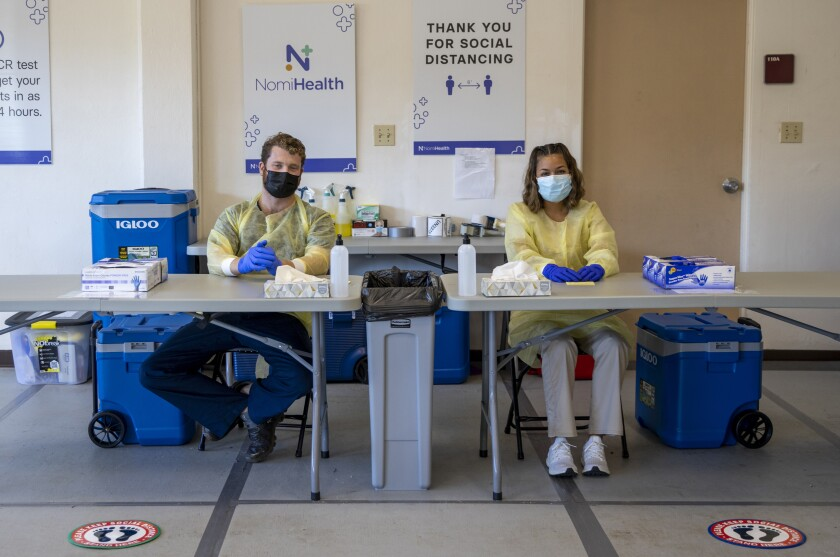 """Two healthcare workers wearing yellow plastic suits around them, masks and blue gloves, sit at two tables with gloves, napkins and sanitizer with stepping symbols on the floor in front of them and signs that say """"Nomi Health"""" and """"thank you for social distancing"""" behind them."""