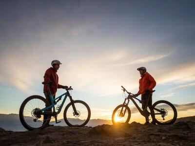 Riders standing on a trail next to their e-mountain bikes