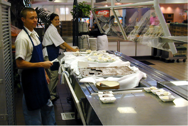 This is picture of two student workers a dessert bar in the cafeteria, preparing dessert for students.