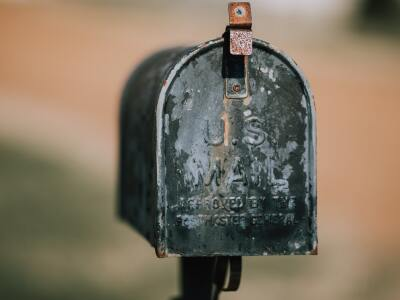 A photo of an old rusty U.S. mailbox.