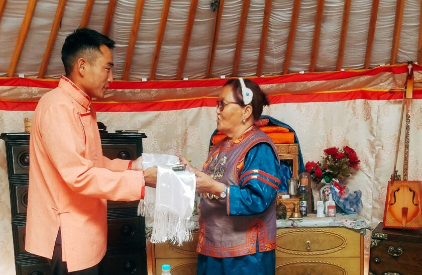Ganbaatar is given something in a white scarf by a woman wearing traditional Mongolian clothes in a yurt.