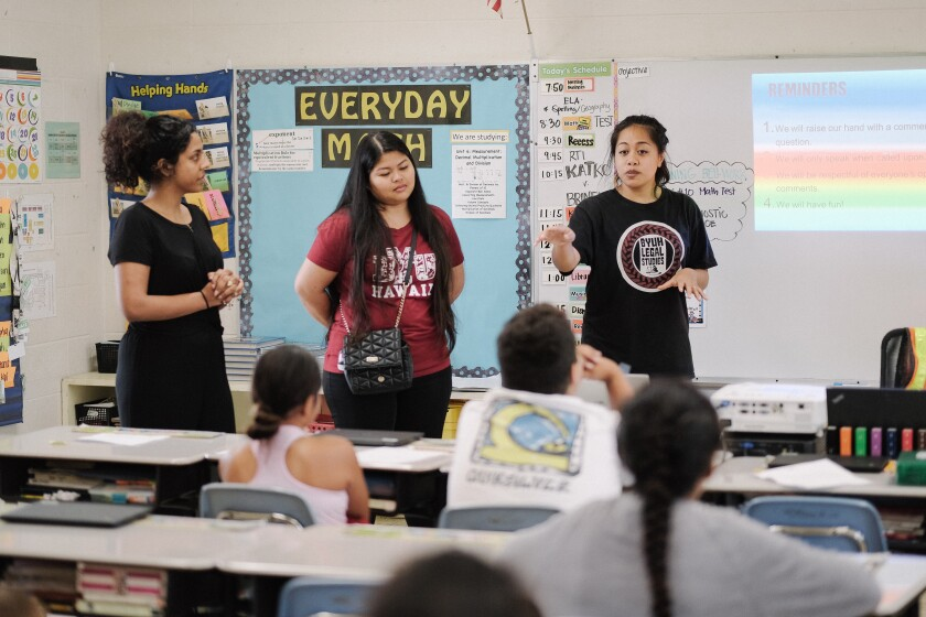 Leilani teaches with fellow BYUH students to a classroom full of younger students.
