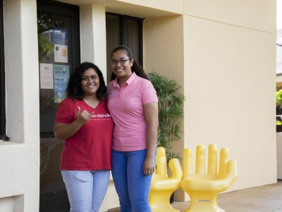 Two employees standing in front of the Alumni & Career Services' Office at the Canon Activities Center