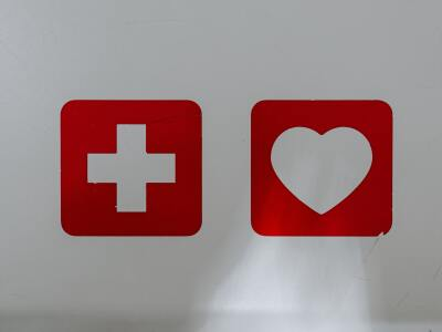 A white background with a red cross and a red heart painted on
