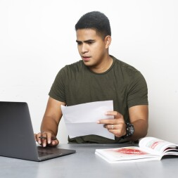 A student sitting at a desk with a laptop, paper and book