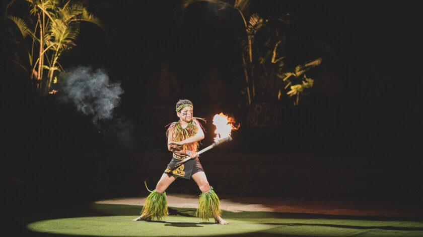 A boy fireknife dancing wearing a black with yellow worded lavalava with green leaves around his legs, neck and headband of it with a spotlight on him.