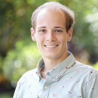 A portrait of Garrett Jensen smiling at the camera with blurred green plants in the background.